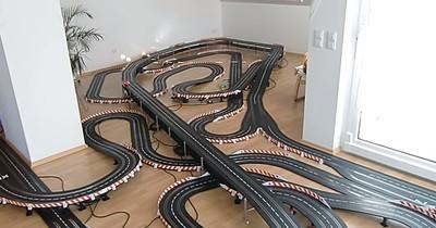 Mann baut riesige Carrera-Bahn durch die komplette Wohnung