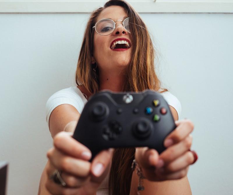 Mädchen mit Xbox controller in der hand, Brille, rote lippen