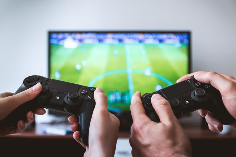 zwei playstation kontroller, tv im hintergrund fußball
