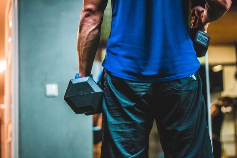 Ein Mann trainiert mit Gewichten