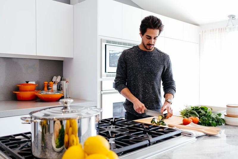 Mann schneidet Gemüse für gesunde Ernährung