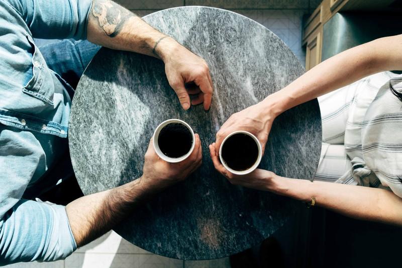 Mann- und Fraunehand mit Kaffee