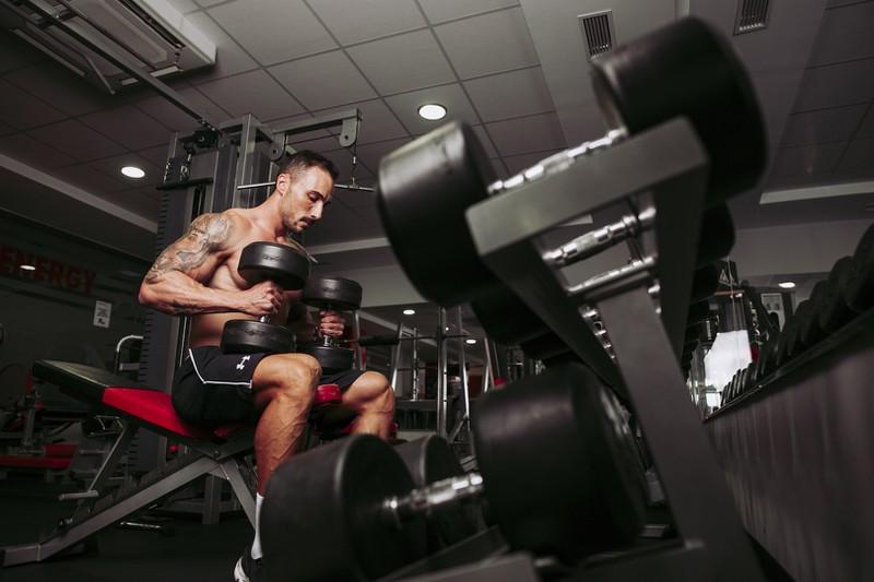 Ein Mann, der im Fitnessstudio trainiert, während er sich vermutlich an die Regeln hält.