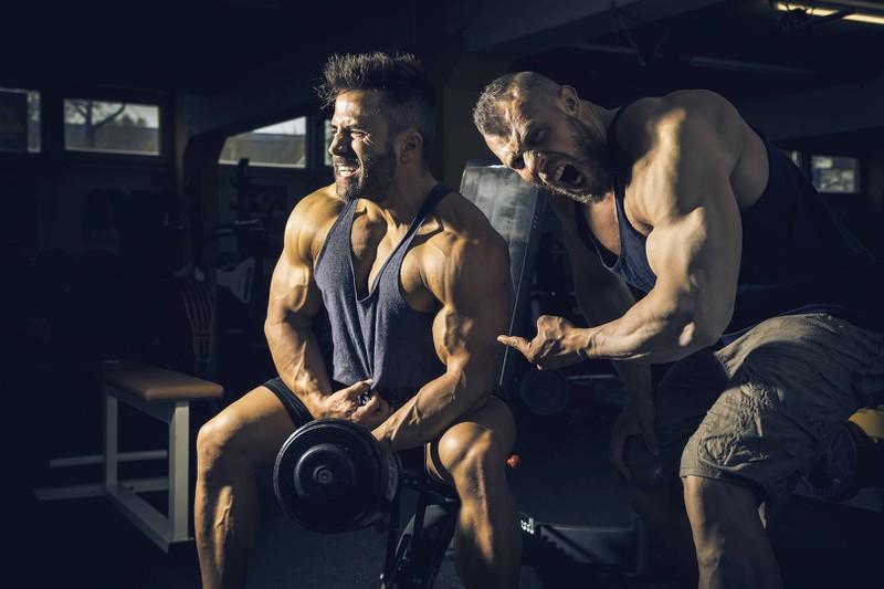 Zwei Männer, die eines der NoGos im Fitnessstudio machen, nämlich das Stöhnen während des Trainings.