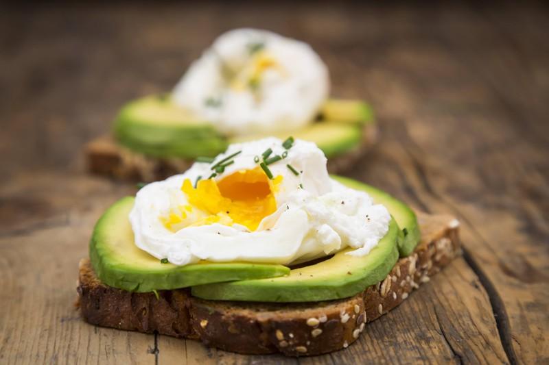 Man sieht ein Avocado-Brot mit Ei, welches sehr gut für den Muskelaufbau ist, da das Ei eine sehr hohe biologische Wertigkeit und somit viel Eiweiß besitzt