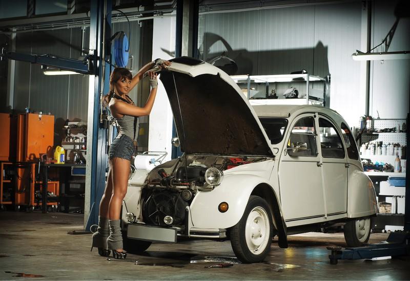 Eine Frau steht in einer Auto-Werkstatt und inspiziert den Wagen