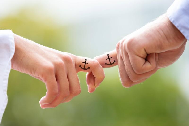 Ein Mann trägt ein Mini Anker Tattoo auf seinem Nacken