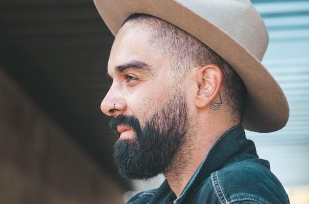 Mann mit grafischem Mini Tattoo hinter dem Ohr