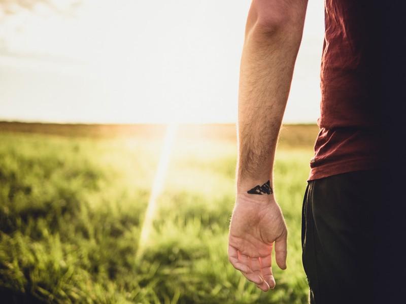 Mann trägt Berge auf dem Handgelenk tätowiert