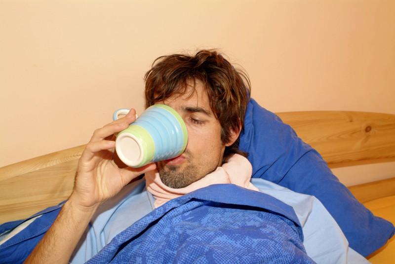 Ein Mann liegt im Bett und trinkt Tee gegen seine Erkältung