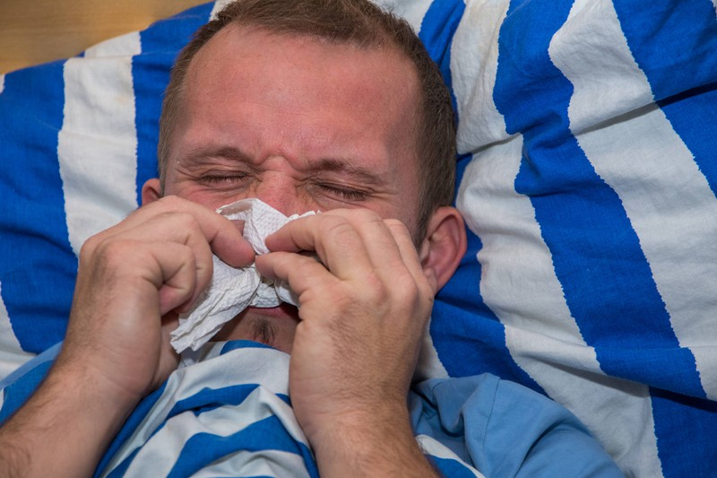 Ein Mann liegt mit einer schweren Erkältung im Bett und sucht etwas, das ihm hilft