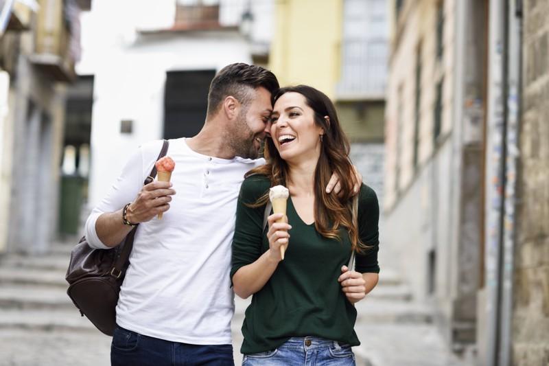 Ein Mann, der seiner Freundin ein Kompliment ins Ohr flüstert