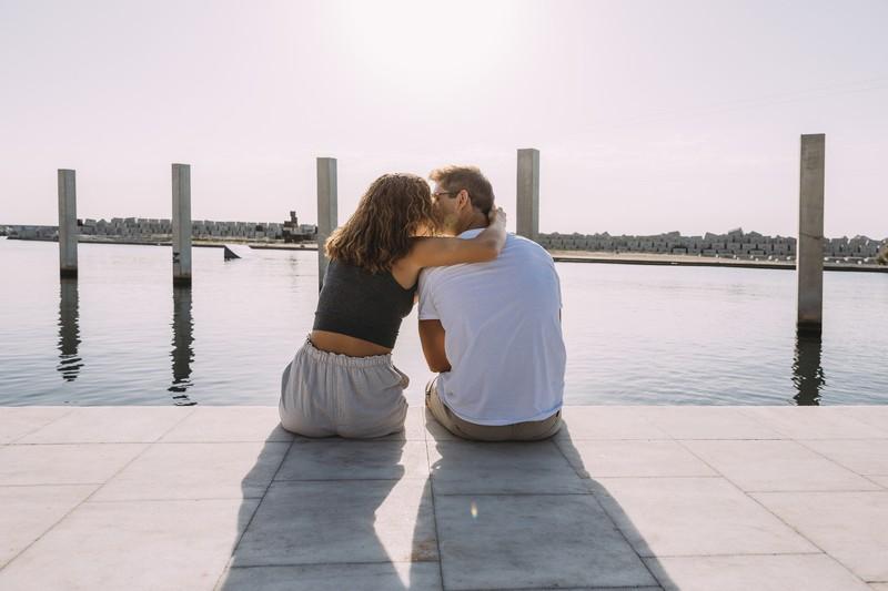 Eine verliebte Frau küsst ihren Freund, der am Wasser sitzt