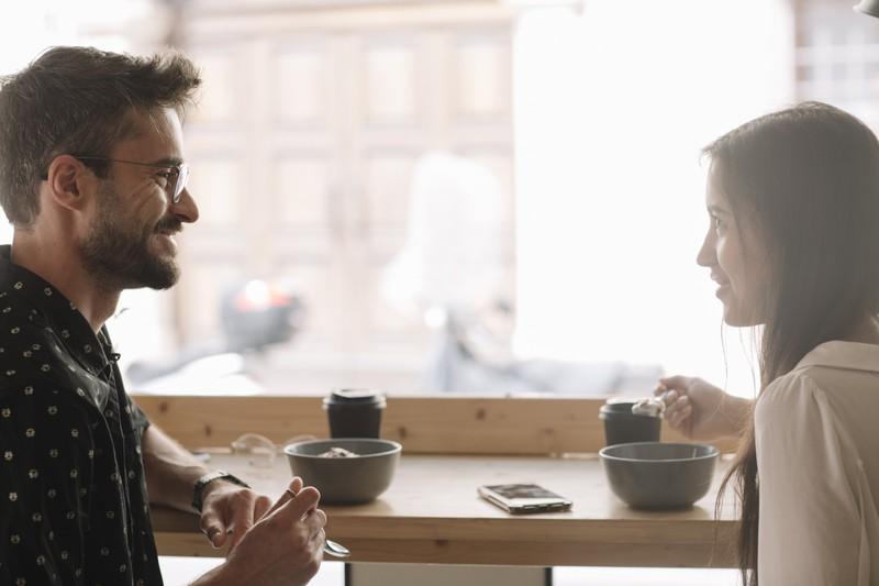 Man erkennt einen Mann, der gerade versucht seine Flirtsprüche im Gespräch mit einer Frau unterzubringen