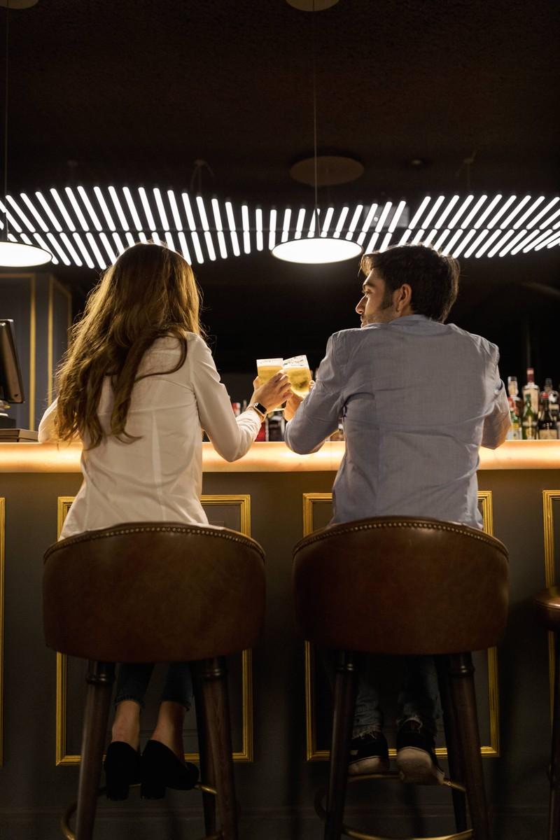 Man sieht einen Mann, der eine Frau auf einen Drink eingeladen hat