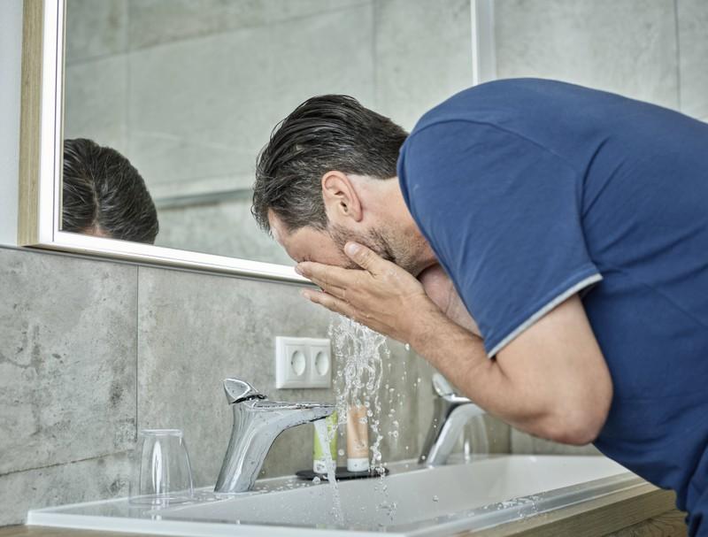 Man sieht einen Mann, der sein Gesicht nur mit Wasser und Seife wäscht, was ein Fehler ist