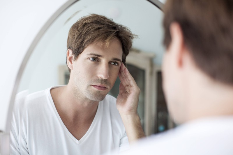 Man sieht einen Mann, der seine Haut betrachtet und überlegt welche Fehler er bei der Gesichtspflege begeht