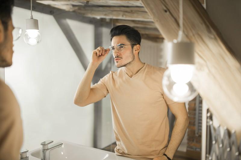 Man sieht einen Mann mit Brille, der womöglich eine Augencreme verwendet