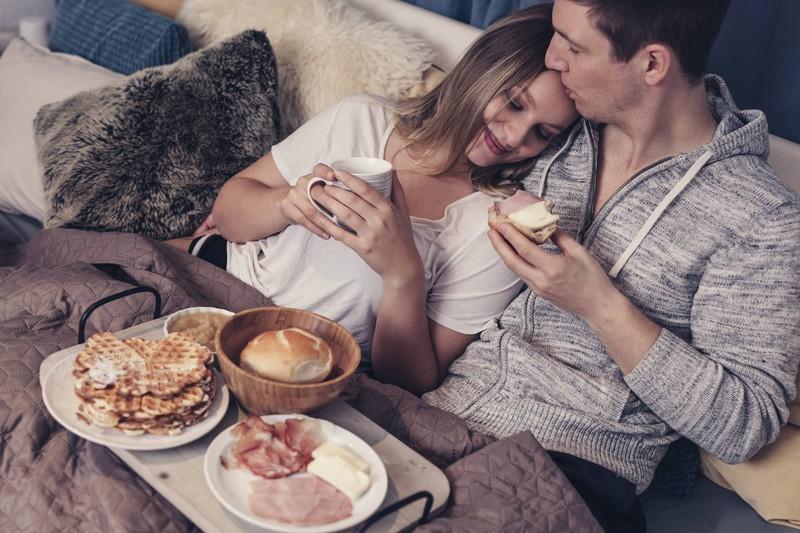 Der Mann frühstückt mit seiner Freundin am Valentinstag im Bett