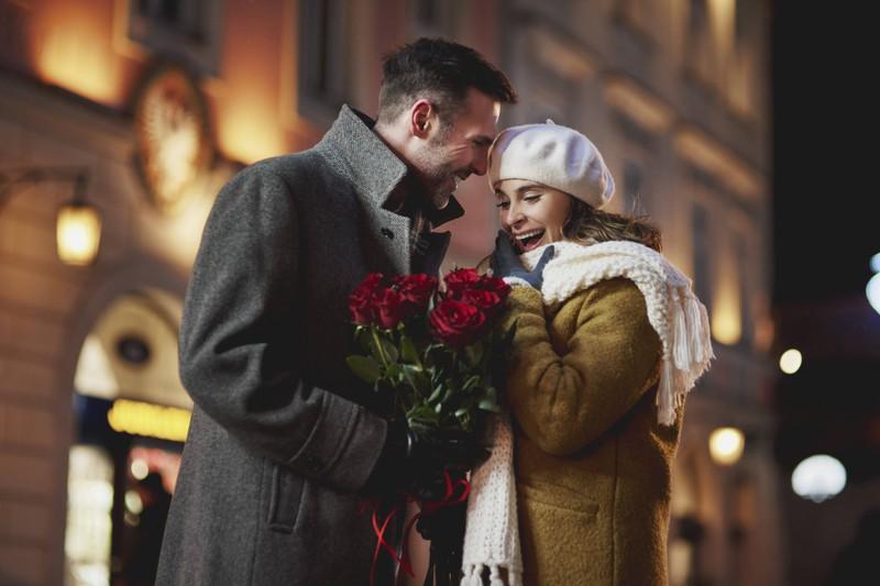 Ein Mann schenkt seiner Freundin Rosen zum Valentinstag.