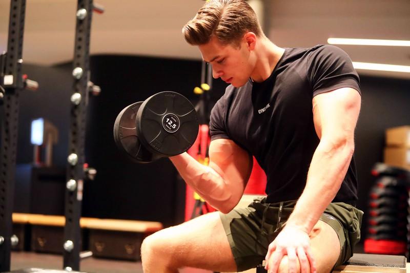 Auf dem Foto ist ein Mann zu erkennen, der für seinen Muskelaufbau trainiert und vermutlich später ein Ei isst