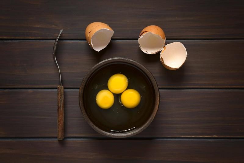 Auf dem Foto sieht man eine Schale mit drei rohen Eiern, die dazu führen können dass Das Biotin schlechter aufgenommen wird