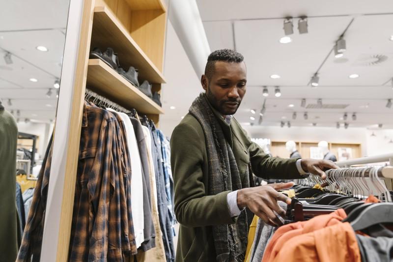 5 Tricks für schüchterne Männer um Frauen ohne Ansprechen aufzufallen: Ein Mann sucht sich gute Kleidung aus.