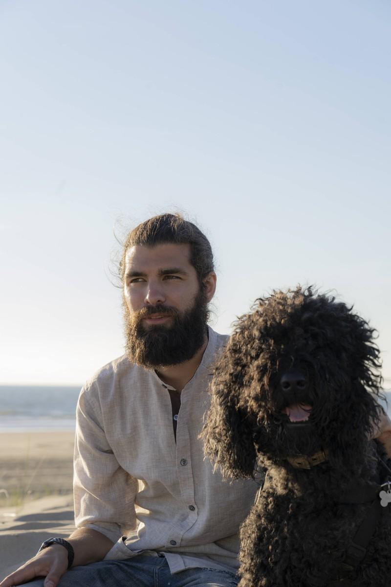 Das Foto illustriert einen Mann mit Bart und Hund, wobei der Hund nicht so dreckig ist wie der Bart