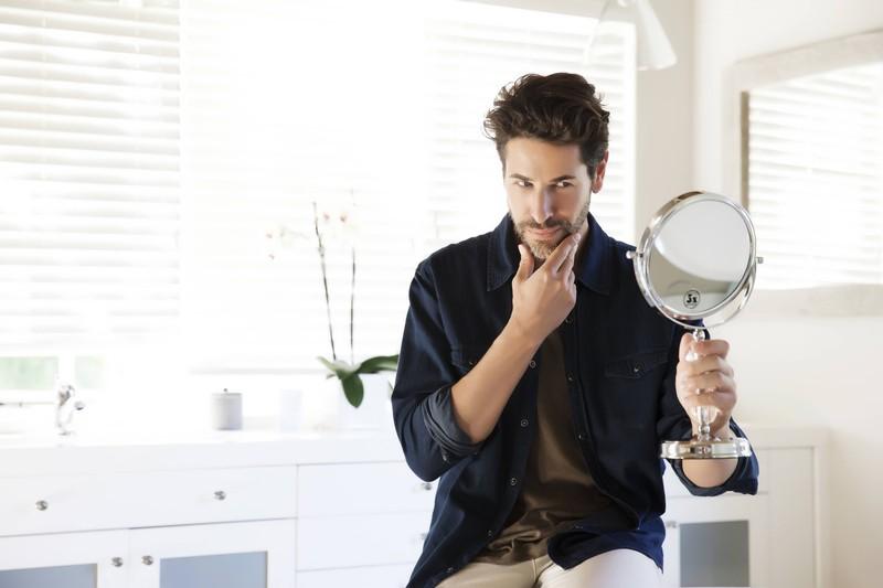 Auf dem Foto ist ein Mann mit Bart zu sehen, der seinen Bartwuchs durch Mittel anregen möchte