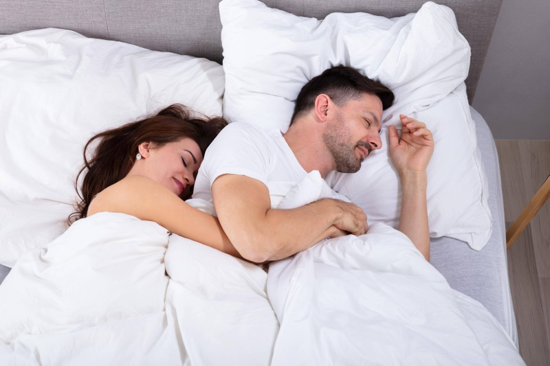 Ein Paar liegt im Bett: Faulige Fürze schrecken Frauen oft ab. Es gibt aber eine Erfindung dagegen.