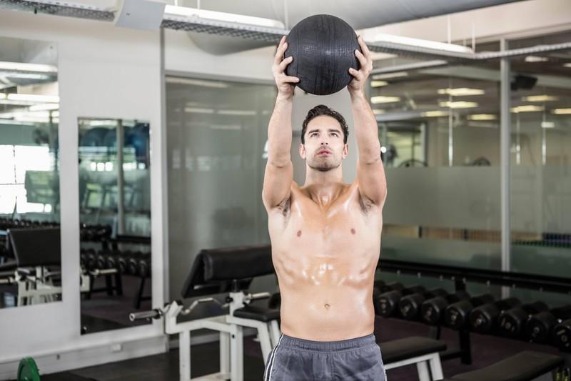 Mann hält Medizinball vor sich