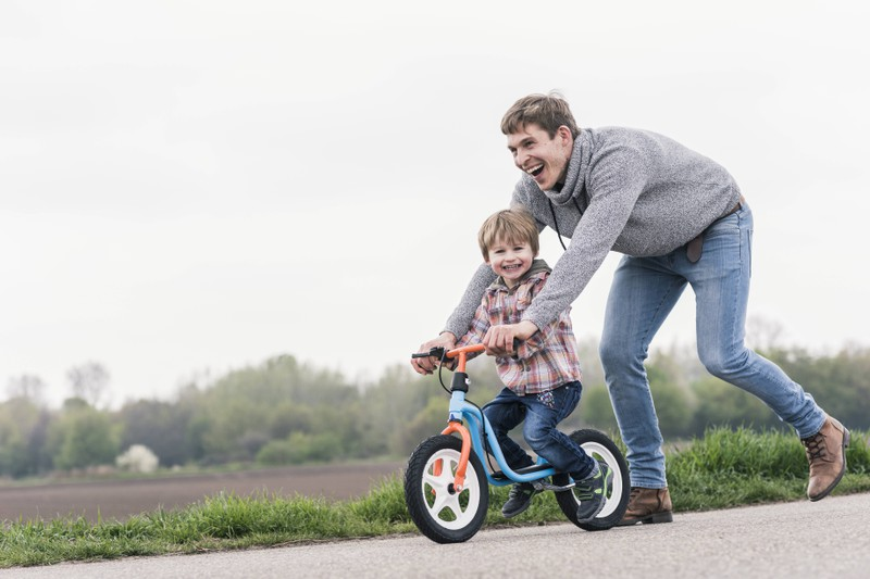 Auf dem Bild ist ein Vater mit seinem Kind zu sehen, und er versucht nicht zu übervorsichtig zu sein