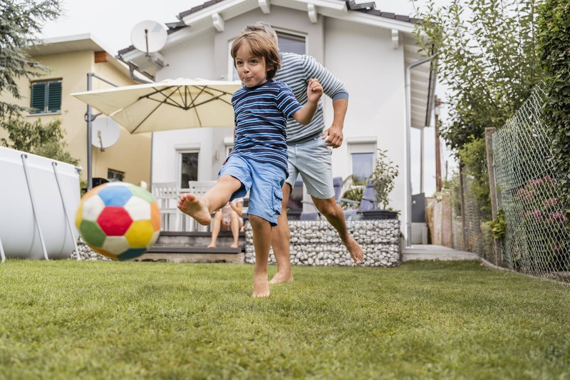 Das Foto illustriert einen Vater, der seinem Kind etwas beibringt, in dem Fall das Fußballspielen