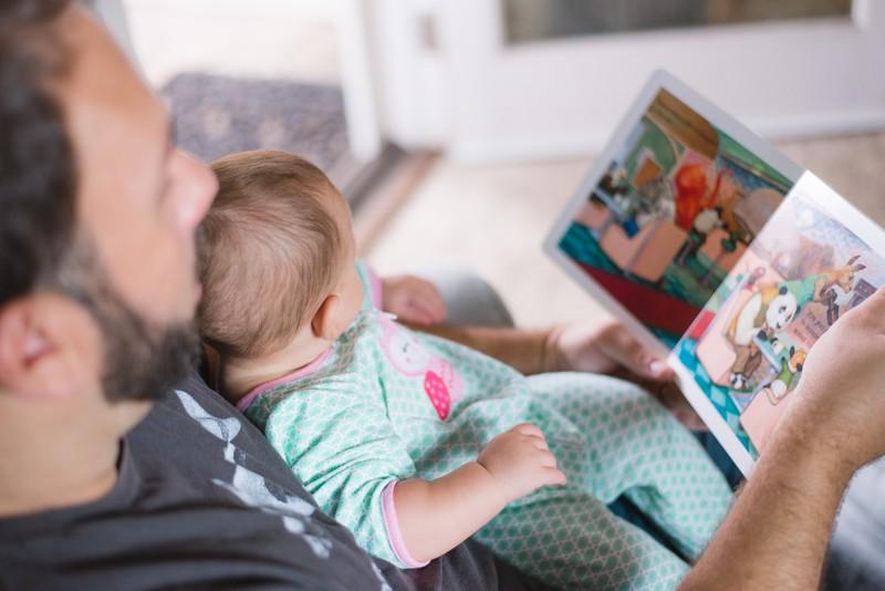Ein Vater, der seinem Kind etwas vorliest, um die Entwicklung seines Kindes zu fördern