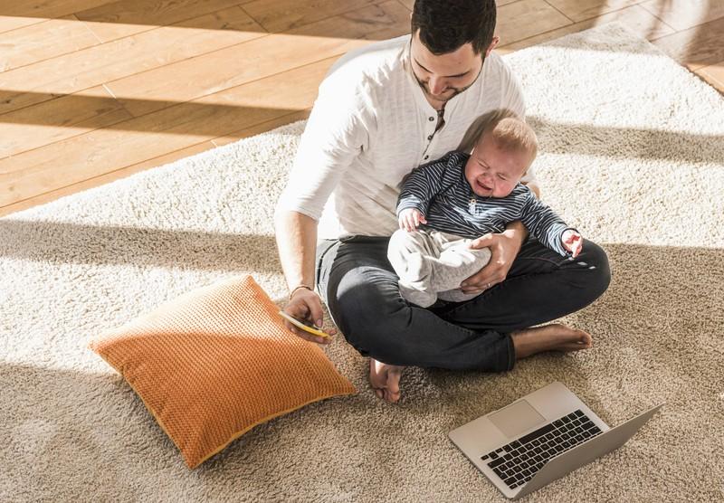 Man erkennt auf dem Bild einen Vater, der etwas überfordert ist, weil sein Kind einen Heulkrampf kriegt, er aber Verständnis zeigen sollte
