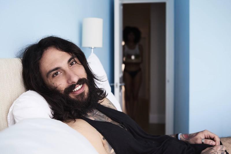 Ein Mann liegt mit langen Haare zuhause. Er muss sich aktuell selbst die Haare schneiden.