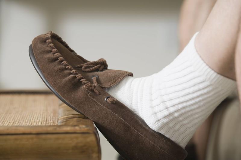 Ein Männerfuß mit Slipper-Schuhen drin