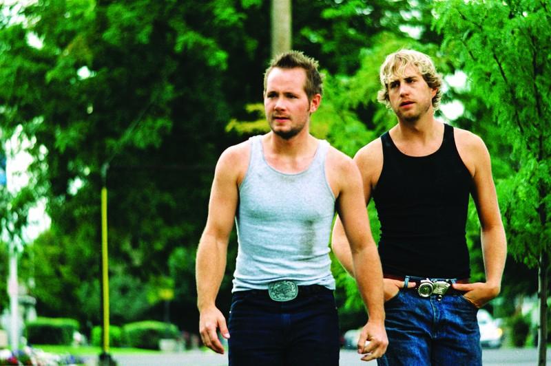 Zwei Männer, die dicke Gürtelschnallen tragen