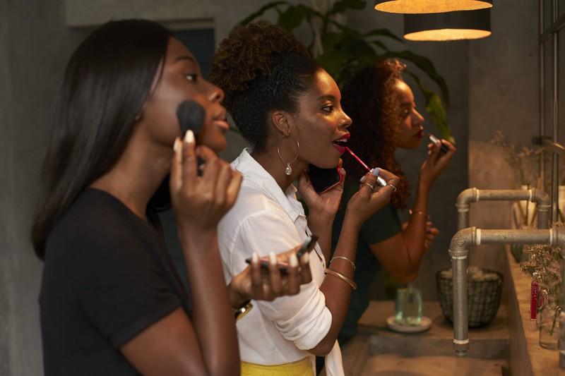 Drei Frauen schminken sich gemeinsam, um danach auszugehen.
