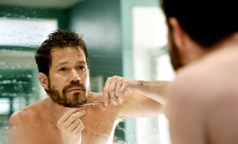 Ein Mann kürzt den Bart mit einer Schere