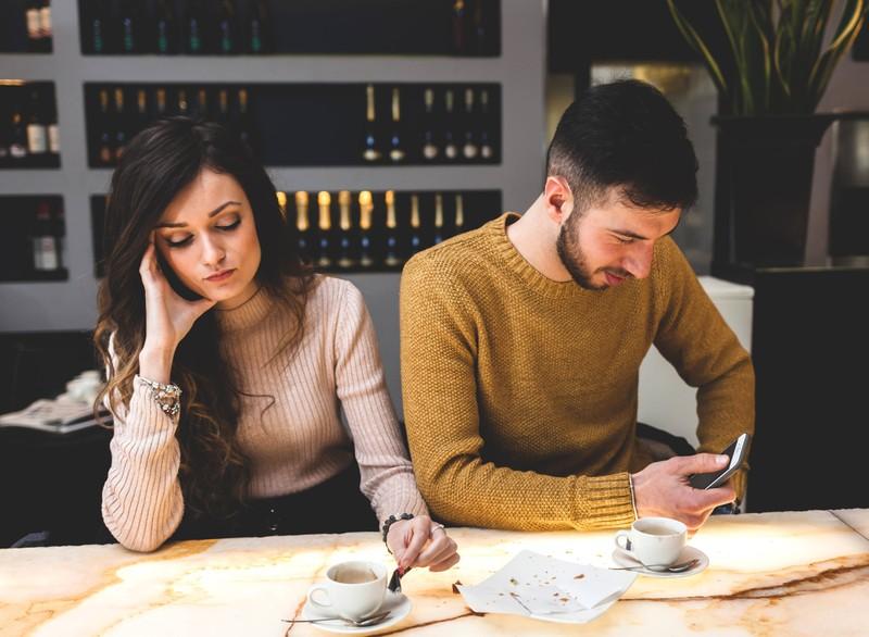 Ein Mann sitzt neben seiner Freundin und textet parallel mit einer anderen Frau