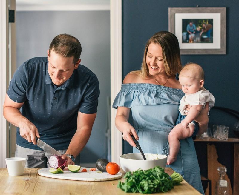 Ein Mann kümmert sich um das Essen, während die Frau sich ums Baby kümmert