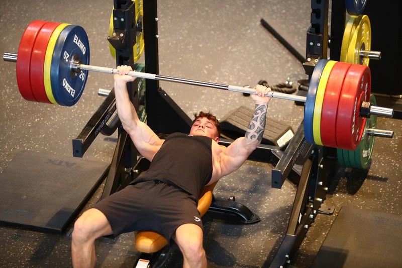 Ein Mann drückt die Bank und braucht für das Training Motivation
