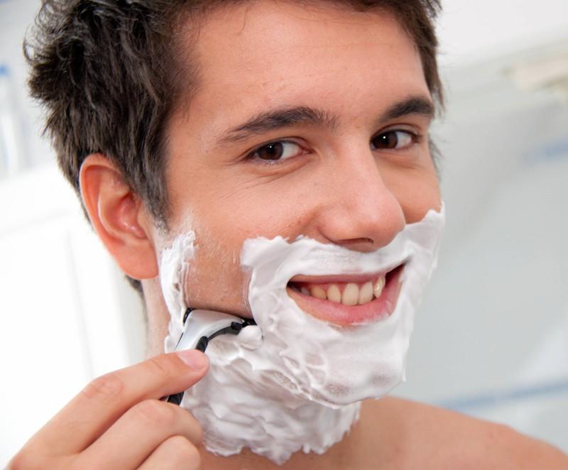 Junger Mann rasiert sich mit Rasierklinge und Rasierschaum im Badezimmer um gepflegt zu wirken