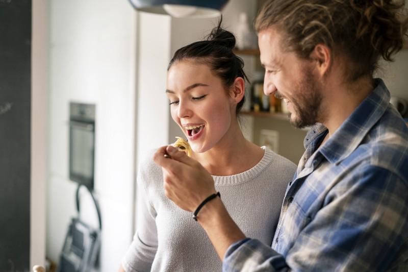 Ein Mann füttert eine Frau mit Pasta