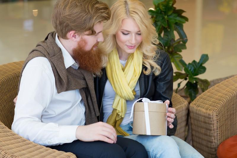 Eine Frau öffent das Geschenk von ihrem Mann zu Weihnachten