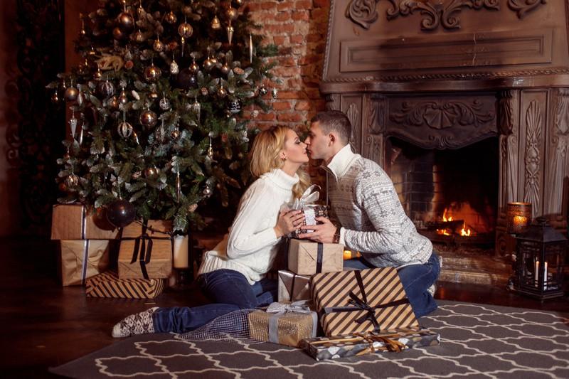 Mann und Frau küssen sich vor dem Weihnachtsbaum