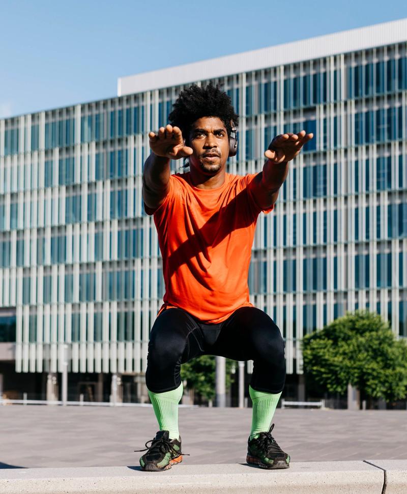 Ohne Geräte oder Fitnessstudio: EIn Mann macht Sprung-Kniebeugen