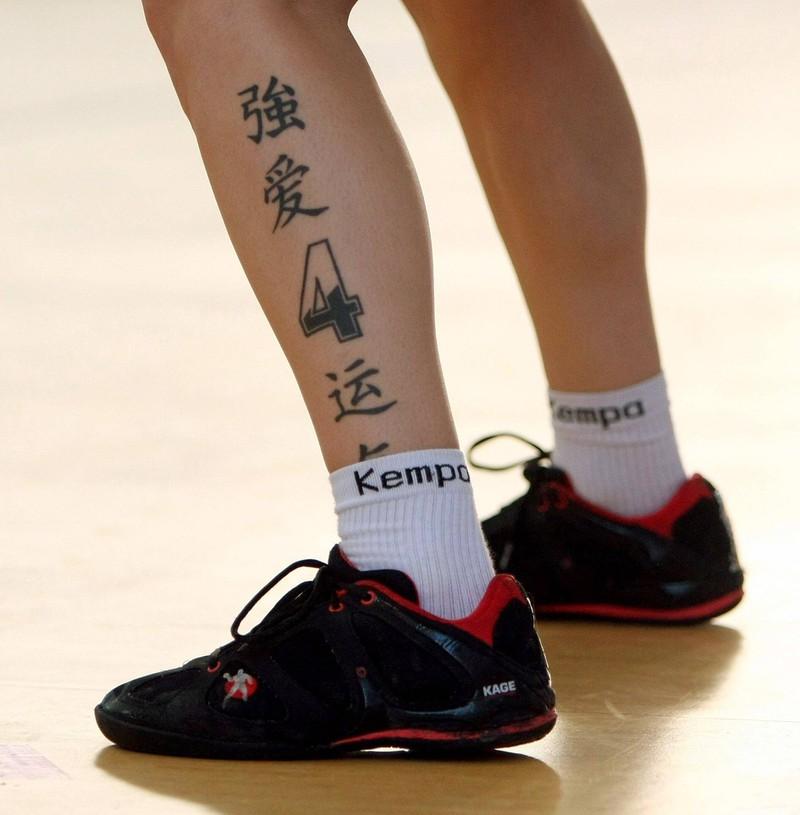 Beine eines tätowierten Mannes, mit chinesischen Schriftzeichen und Symbolen geschmückt