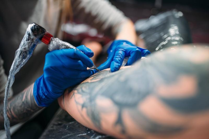 Ein Tätowierer, der in einem Tattoostudio arbeitet und mit Tinte tätowiert